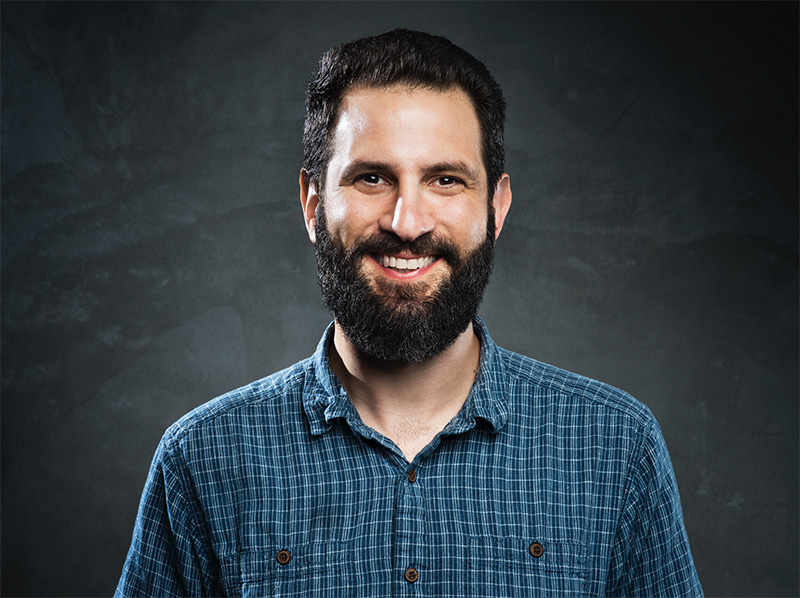 Professional headshot of Hunter Walk wearing a blue, square print, collared shit, smiling through his dark, thick beard.