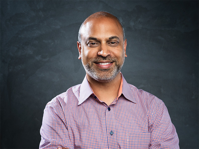 Professional headshot of Satya Patel warmly smiling with arms crossed, wearing a square print collared shirt.